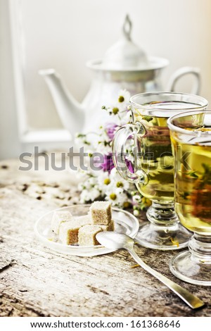 fresh healthy herbal tea in glass cups on wooden texture background - stock photo