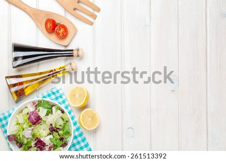 Fresh healthy salad and condiments over white wooden table. View from above with copy space - stock photo