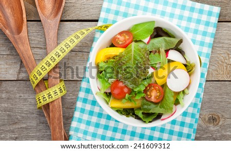 Fresh healthy salad on wooden table and kitchen utensil. View from above - stock photo