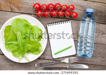 Fresh healthy salad, tomatoes, water bottle and notepad for copy space on wooden table - stock photo