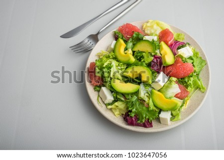 Fresh healthy salad with avocado, grapefruit, lettuce and cheese feta on a white table. Diet food concept