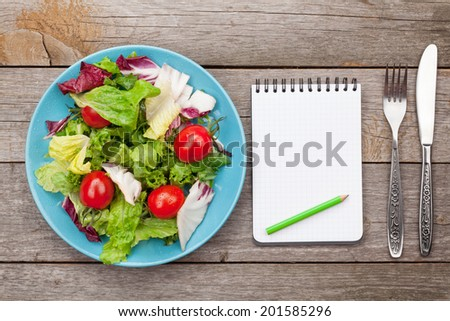 Fresh healthy salad with tomatoes and utensils on wooden table. Healthy food - stock photo