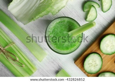 Fresh healthy vegetable smoothie with ingredients on wooden table - stock photo
