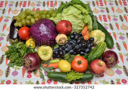 Fresh healthy vegetables and fruits - savoy cabbage, red cabbage, red onion, tomato, pepper, basil, parsley, balm, sage, cucumber, carrot, eggplant, grape, apples, lemon - on apposite tablecloth
