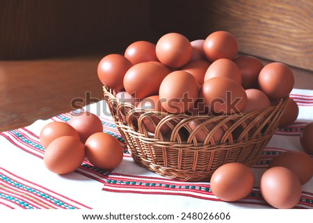 Fresh hen eggs in a woven basket on a wooden background. Easter or diet and nutrition food stock image - stock photo