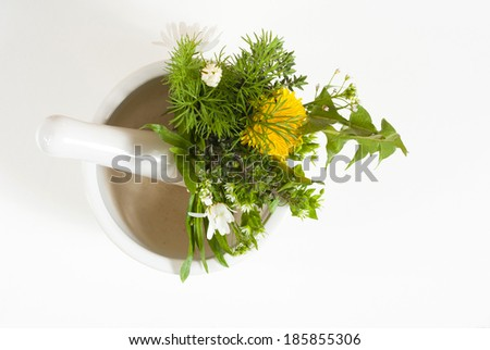 fresh herbal flowers in mortar on white table