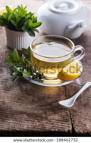 Fresh herbal tea with mint  on wooden background. Fresh mint, lemon. Selective focus. - stock photo