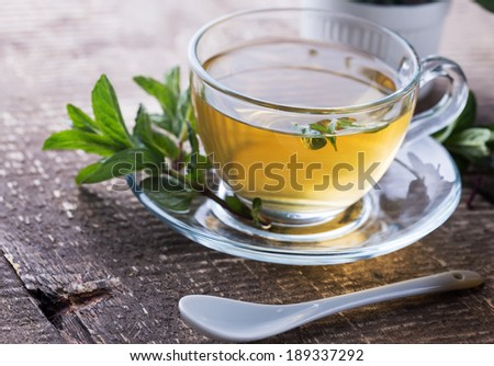Fresh herbal tea with mint  on wooden background.  Selective focus, horizontal. - stock photo