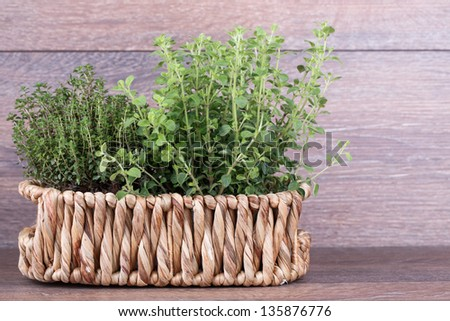 Fresh herbs in basket  on wooden background - stock photo