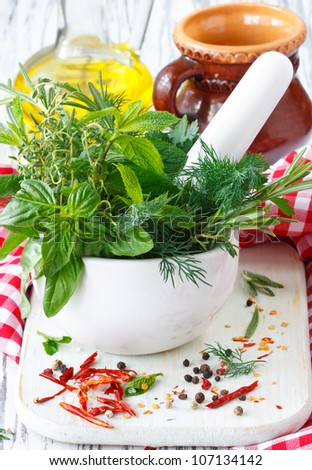 Fresh herbs in white ceramic mortar and spices. - stock photo