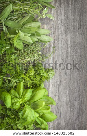 Fresh herbs over grey wooden background - stock photo