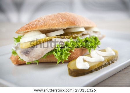 Fresh Herring on a roll. Fish sandwich. - stock photo