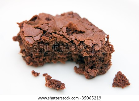 Fresh home-made chocolate brownie with bite-shaped chunk missing, on a white background