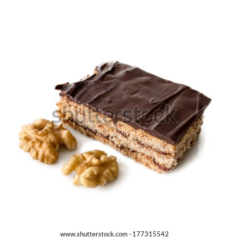 Fresh home made Hungarian layered cake Zserbo with chocolate on top with walnuts isolated on white - stock photo