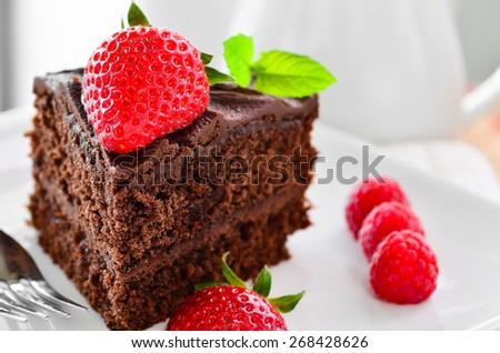 Fresh home made sticky chocolate cake with strawberries and raspberries - stock photo