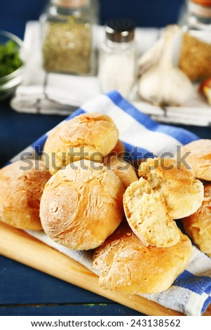Fresh homemade bread buns from yeast dough  and jars with spices, on color wooden background - stock photo