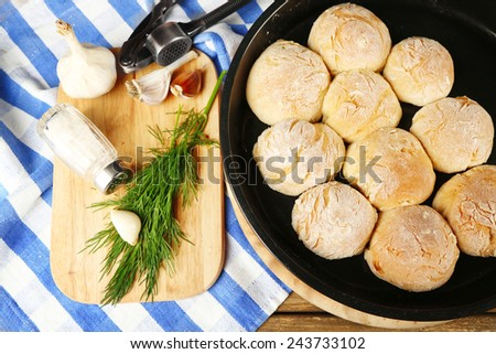 Fresh homemade bread buns from yeast dough on pan and fresh garlic, dill  on cutting board, on color napkin background - stock photo