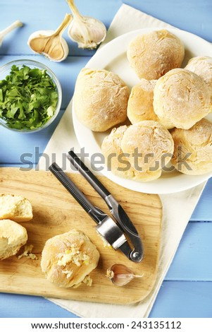 Fresh homemade bread buns from yeast dough on wooden cutting board, on color wooden background - stock photo