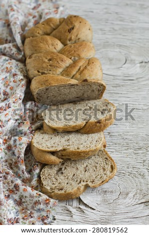 fresh homemade bread with whole wheat flour, flax seeds and pecans on a light wooden surface - stock photo