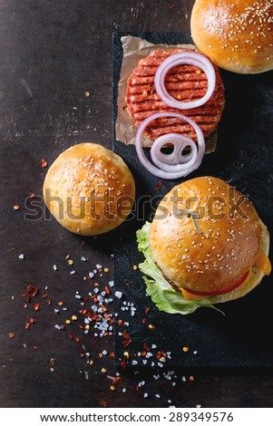 Fresh homemade burger on black slate and raw cutlet and sliced onion, served with sea salt and pepper over dark background. Selective focus. Top view - stock photo