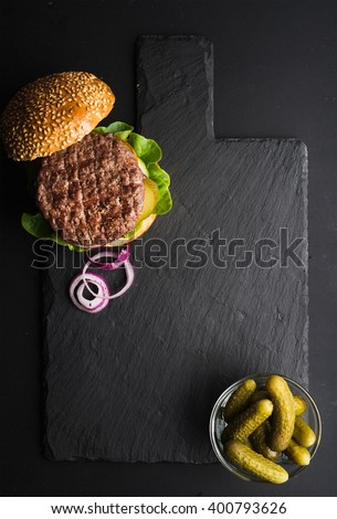 Fresh homemade burger on dark slate stone board, pickles and sliced onion over black background. Top view, copy space - stock photo