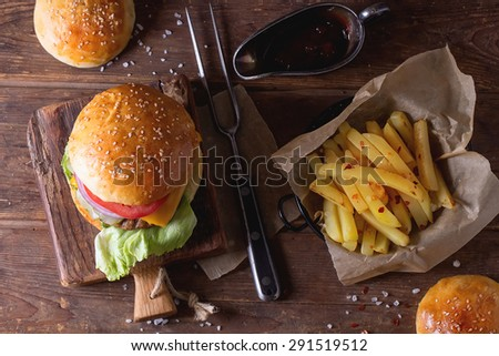 Fresh homemade burger on little cutting board with grilled potatoes, served with ketchup sauce and meat fork over wooden table. Dark rustic style. Top view - stock photo