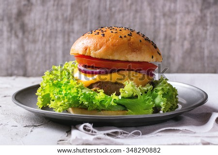 Fresh homemade burger with black sesame seeds in vintage metal plate, served over white plastered table and white textile with gray wooden background. Rustic style. - stock photo