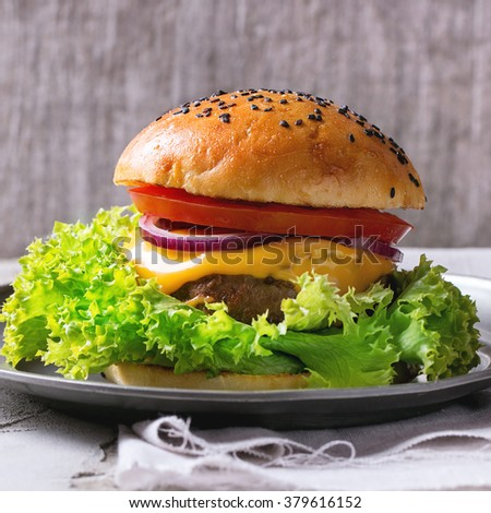 Fresh homemade burger with black sesame seeds in vintage metal plate, served over white plastered table and white textile with gray wooden background. Rustic style.  Square image with selective focus - stock photo