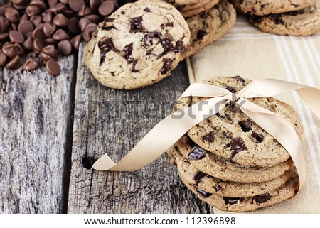 Fresh homemade chocolate chip cookies with chocolate chips and more cookies in the background. Shallow depth of field.