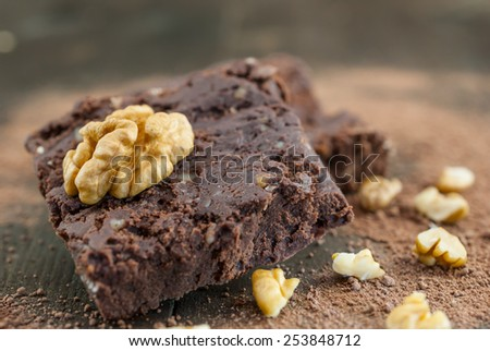 Fresh homemade chocolate pieces on vintage wooden background. Traditional western confectionery with nuts and cocoa. Shallow depth of field - stock photo