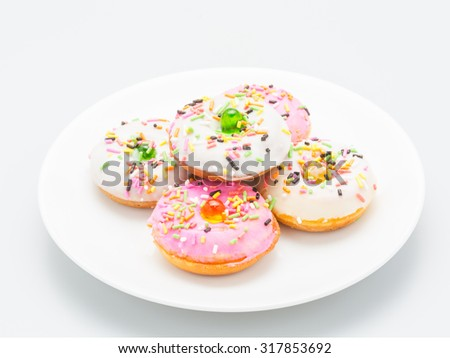 Fresh homemade colorful donuts with icing glaze delicious on white plate - stock photo