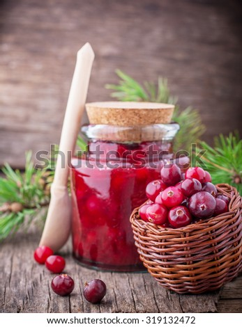 Fresh homemade cranberry sauce in a glass on a dark wooden background with a scattering of ripe berries. selective Focus - stock photo