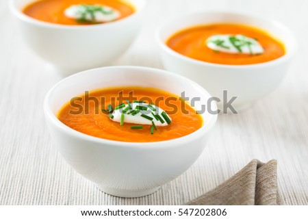 Fresh homemade cream of carrot soup with dollop of cream or yogurt and chives on top served in bowls, photographed with natural light (Selective Focus, Focus in the middle of the first soup)