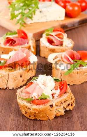 Fresh homemade crispy Italian antipasto called Bruschetta topped with tomato, garlic and basil on wooden board (Selective Focus, Focus on the tomato piece in the front) - stock photo