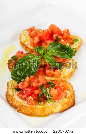 Fresh homemade crispy Italian appetizer called Bruschetta topped with tomato, garlic and basil - stock photo