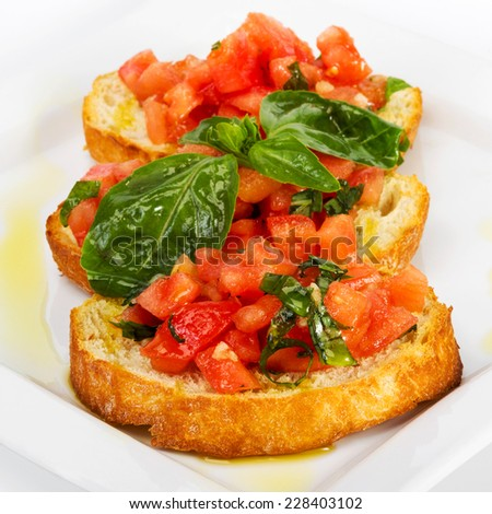 Fresh homemade crispy Italian appetizer called Bruschetta topped with tomato, garlic and basil. Selective focus - stock photo