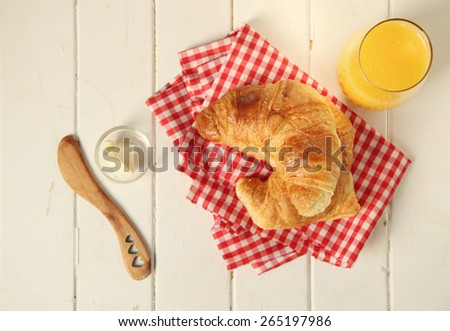 Fresh homemade croissant on checkered tableclothe with butter and a glass of orange juice.  Top view. - stock photo