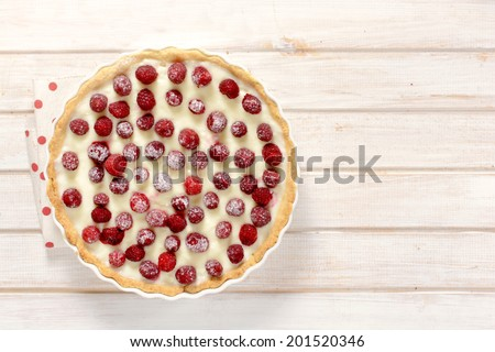 Fresh homemade fruit tart on the wooden table and blank space on right side  - stock photo