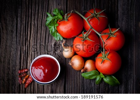 Fresh homemade ketchup and ingredients composition. Vegetables and sauce photography taken on rustic old table. - stock photo