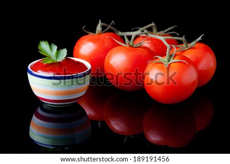 Fresh homemade ketchup and tomatoes composition. Vegetables photography taken on black surface. - stock photo