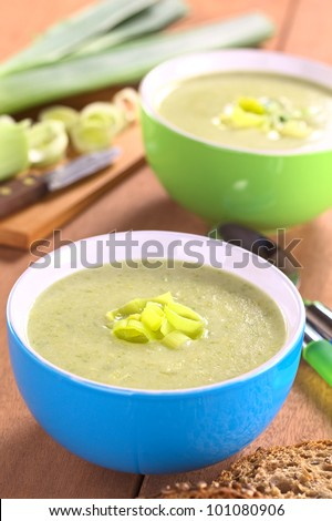 Fresh homemade leek soup in colorful bowls (Selective Focus, Focus on the leek rings on the top of the soup)