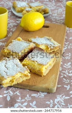 Fresh homemade lemon tarts on wooden board - stock photo