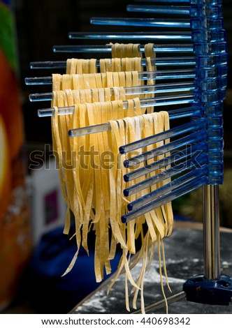 Fresh homemade noodles drying in the kitchen. Still life with raw homemade pasta - traditional Italian cuisine. - stock photo