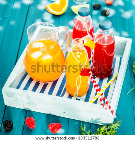Fresh homemade orange and berry juice served in glass bottles and chilled with ice in a glass jug on a colorful, blue wooden picnic table on a wooden tray - stock photo