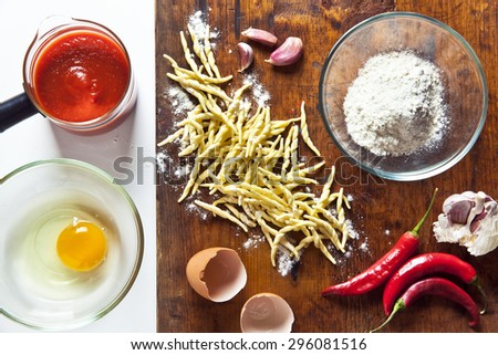 fresh homemade raw  pasta Trofie with  food ingredients: eggs, flour, olive oil, peppercorns in a grinder for spices, garlic and hot peppers. on a wooden background. tomato sauce - stock photo