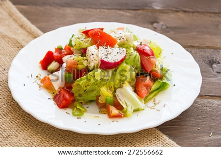 Fresh homemade salad with lettuce, green onions, radishes, tomatoes, red pepper and feta cheese - stock photo