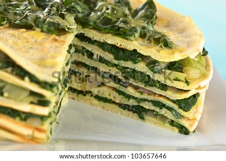 Fresh homemade savory crepes layered with chard (mangold) and onion with cheese on top (Selective Focus, Focus on the right front part of the topping and running down through the cake) - stock photo