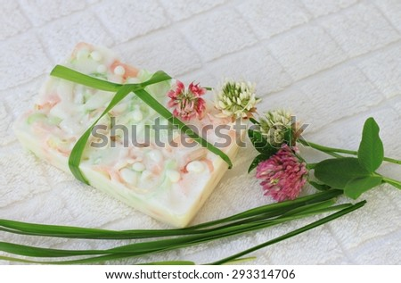 fresh homemade soap herbal clover flower bathroom natural cosmetics  leaves white terry towel nature remedy, soap bar decorated pretty bow - stock photo