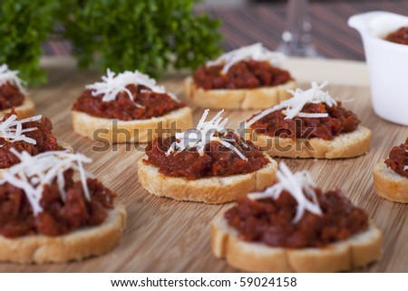 Fresh homemade sun dried tomato tapenade on toasted baguette topped with fresh grated cheese.