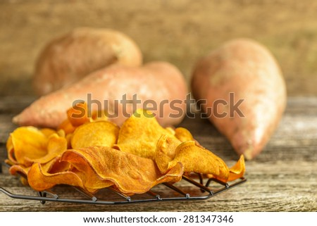 Fresh homemade sweet potato chips on a rustic background. - stock photo